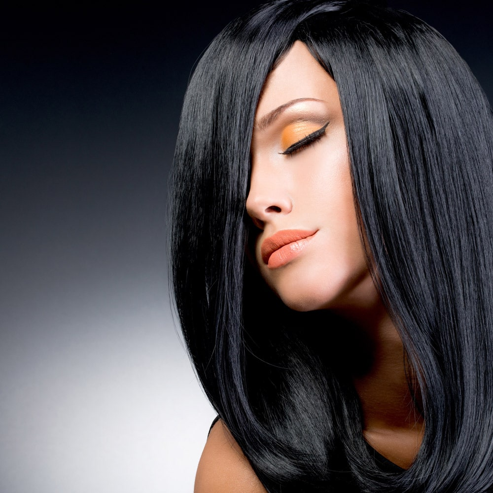 model with straight black hair covering right side of face