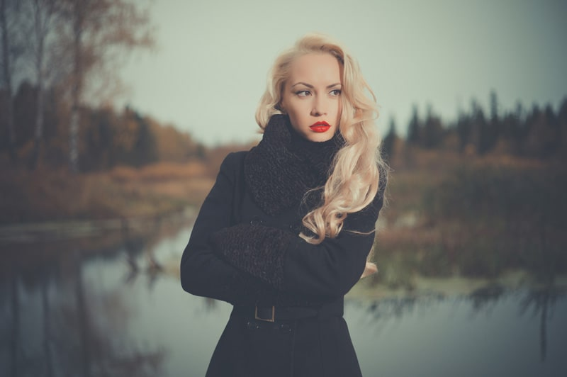 model with long blonde hair standing outside in black coat near pond