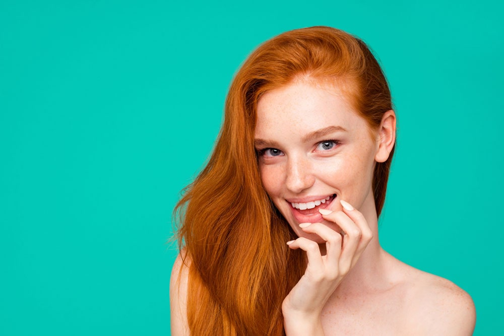 model with red hair smiling with fingers resting along side of chin