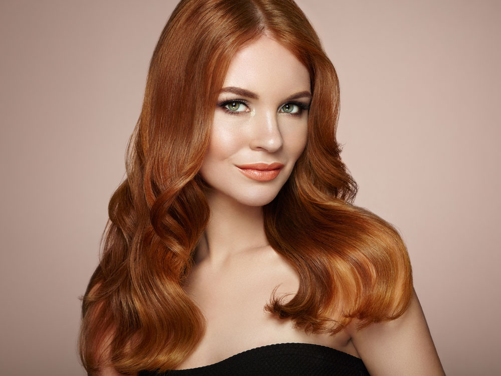 model with deep red hair positioned forward over shoulders wearing black top