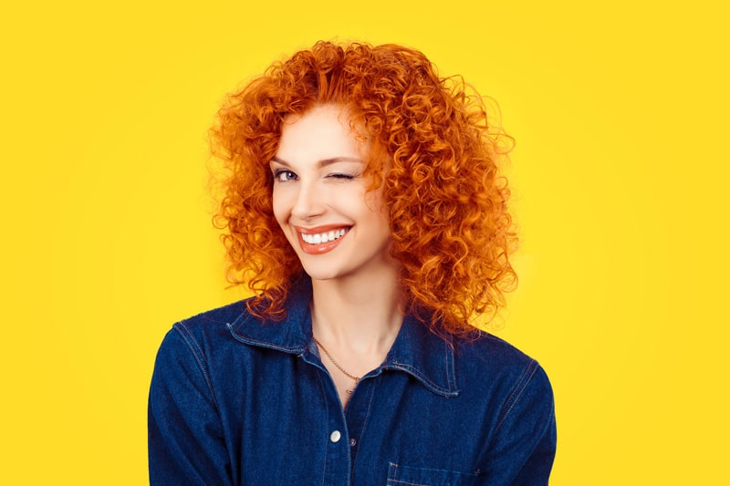 model with bright red curly hair in blue denim shirt smiling and winking at camera