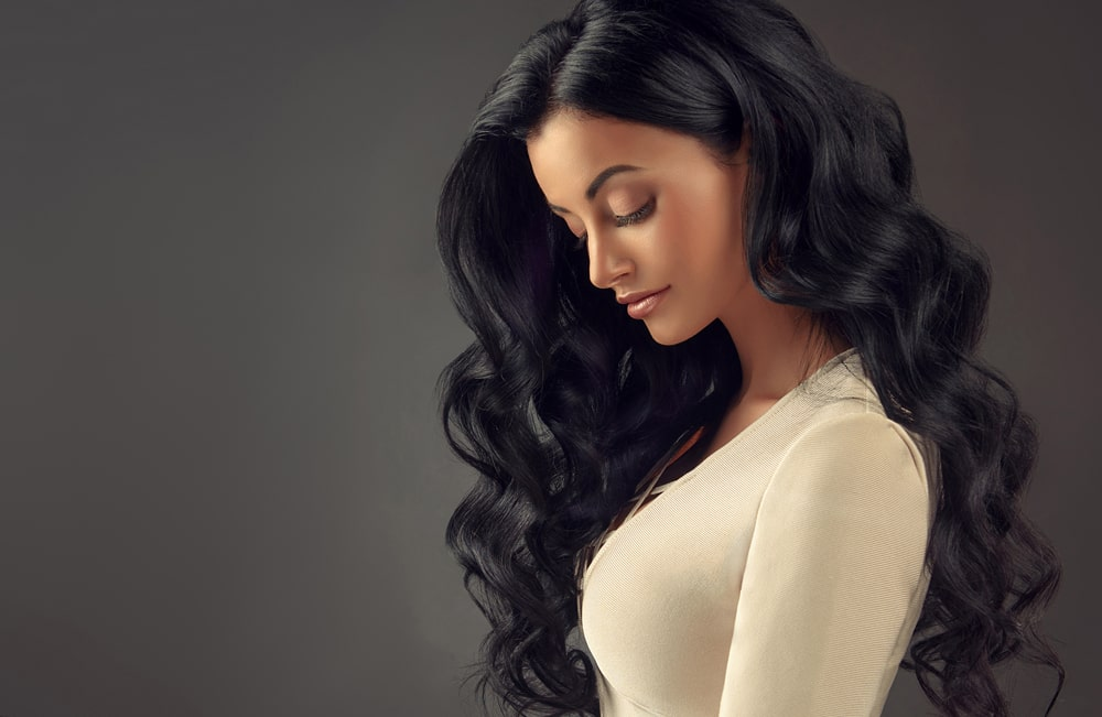 model with long black wavy hair posed in silhouette