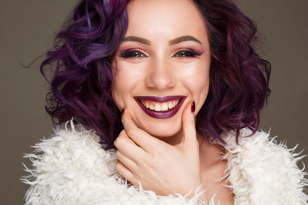 model smiling with dark lilac hair