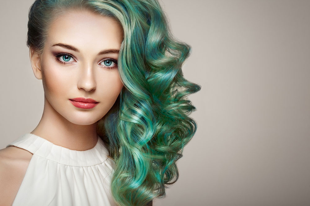 model with wavy bright teal colored hair swept over to left side
