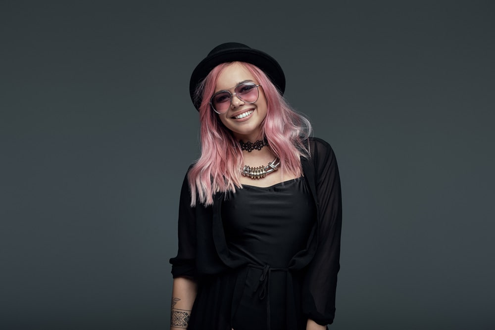 model wearing hat and sunglasses with shoulder length pastel pink wavy hair