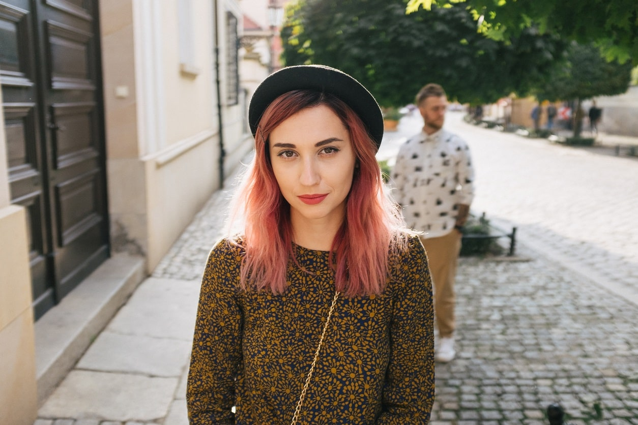 young woman wearing hat outdoors with long rose color dyed hair