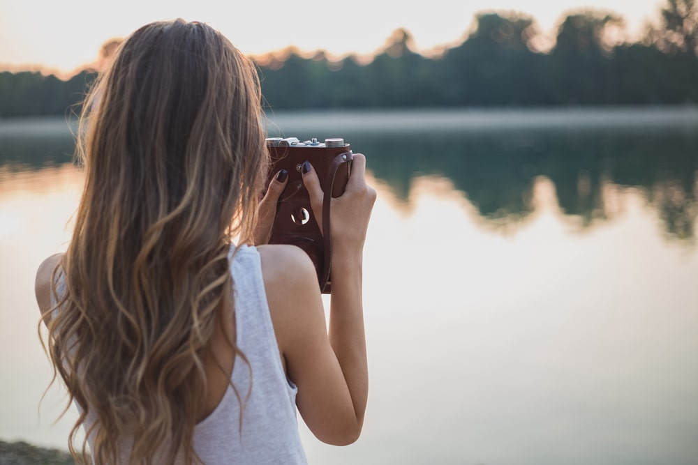 model with sombre hair highlights taking photo of still lake
