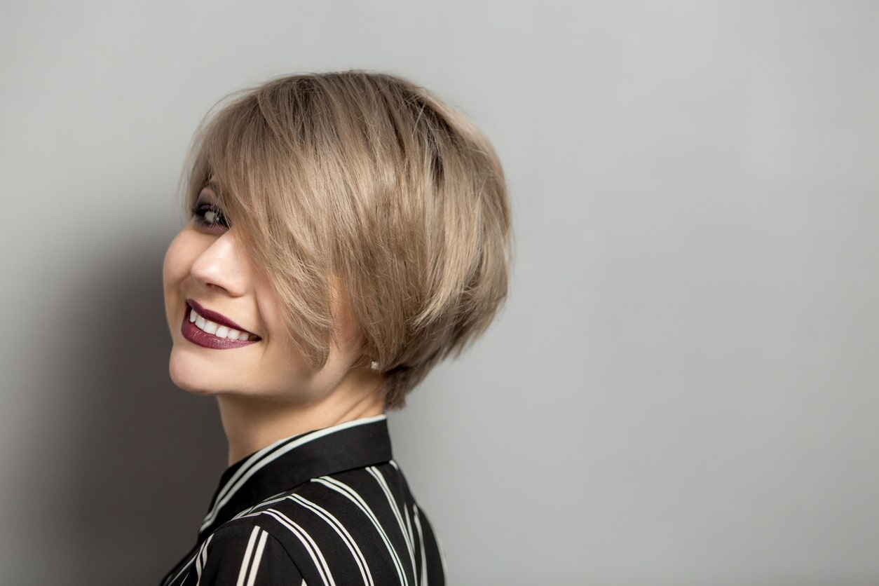 woman with blonde bob cut posing in front of grey background