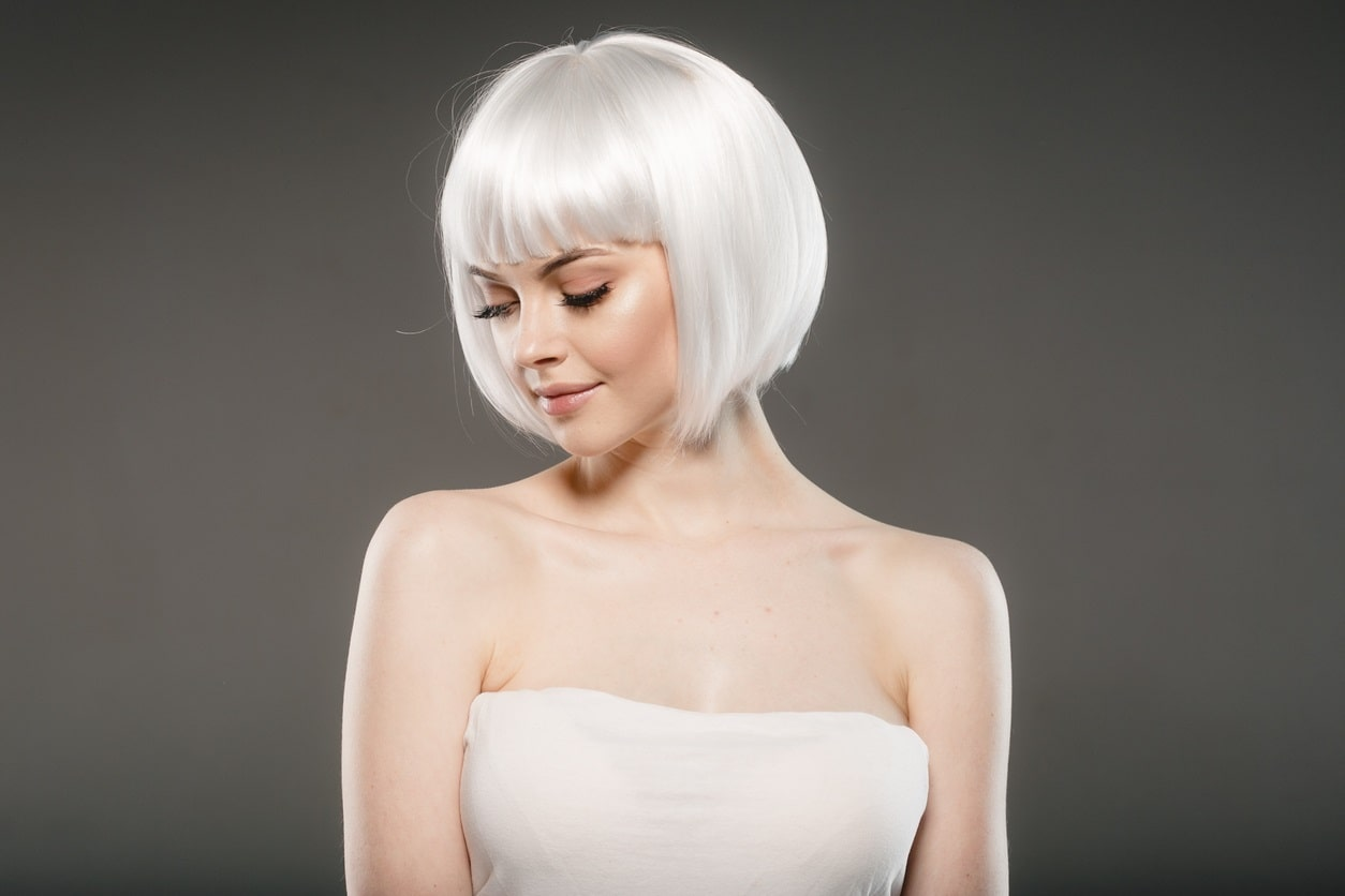 model with platinum blonde bob cut posing in front of dark grey background