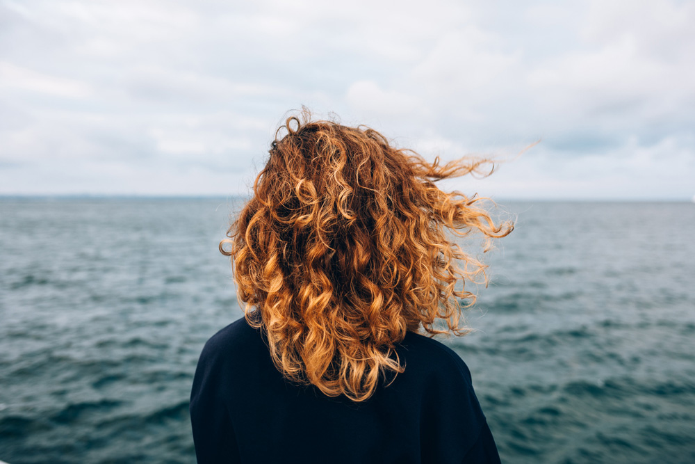 model with strawberry blonde hair facing the ocean