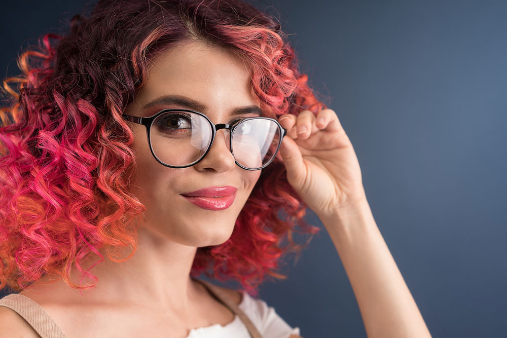model with curly bright pink dyed hair