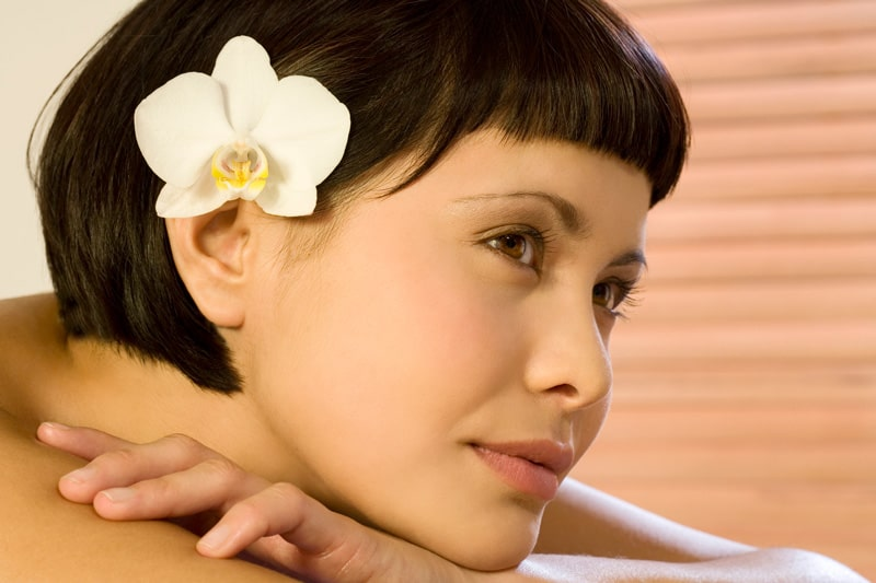 brunette model with short bangs, wearing white orchid in hair