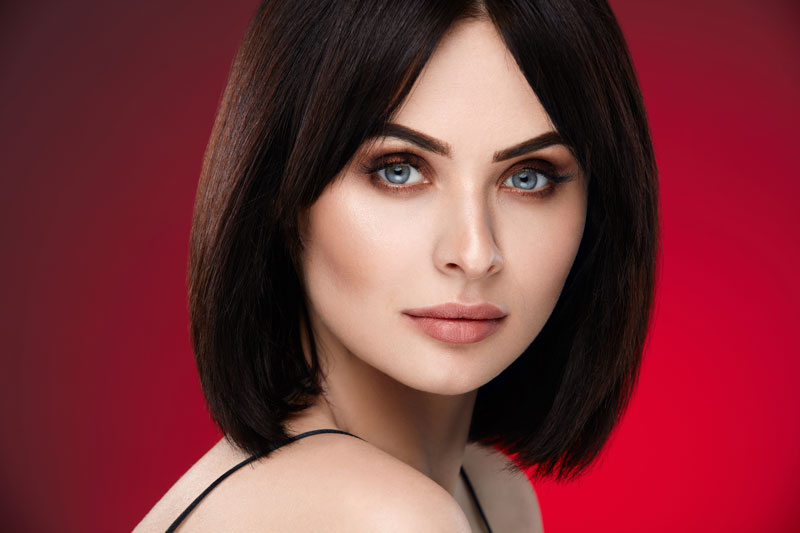 model with dark brown blunt bob cut posing in front of deep red background