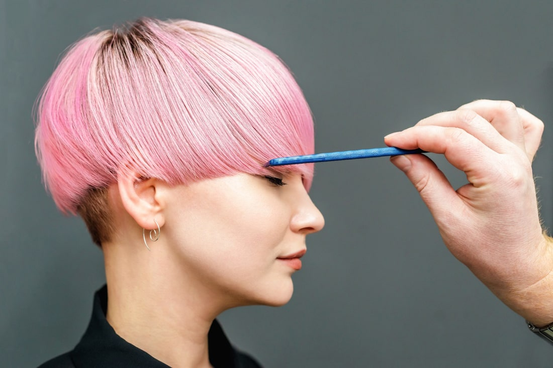 model with bright pink bowl cut being combed by hairstylist