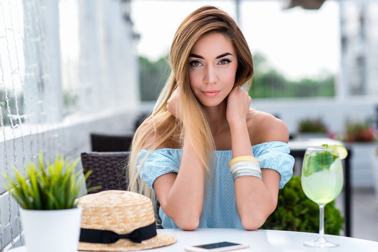 Model seated at table holding back hair with wide blonde highlights on brunette hair