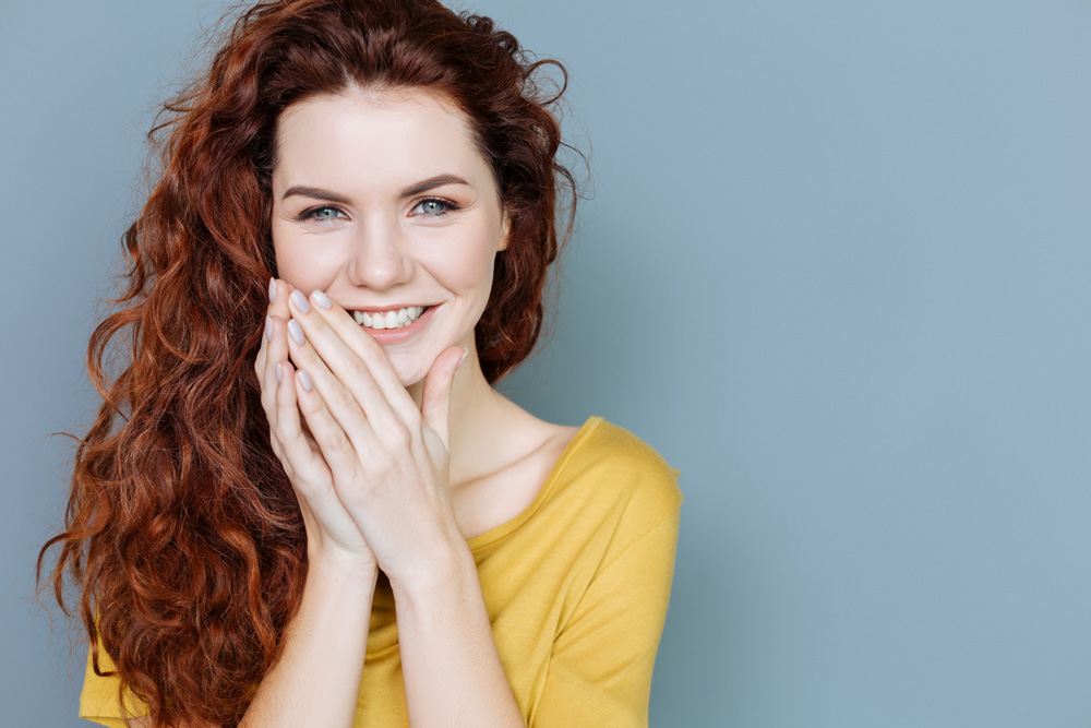model smiling with hands resting on lower face with long curly cinnamon colored hair