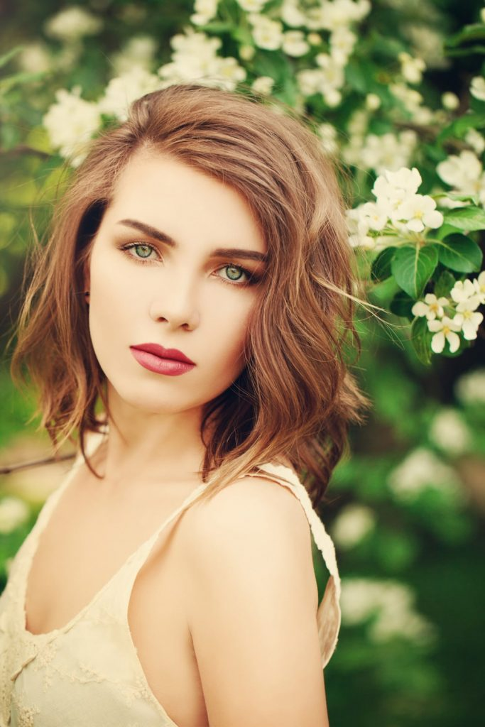 model with shoulder length brown wavy hair outside near flowering tree