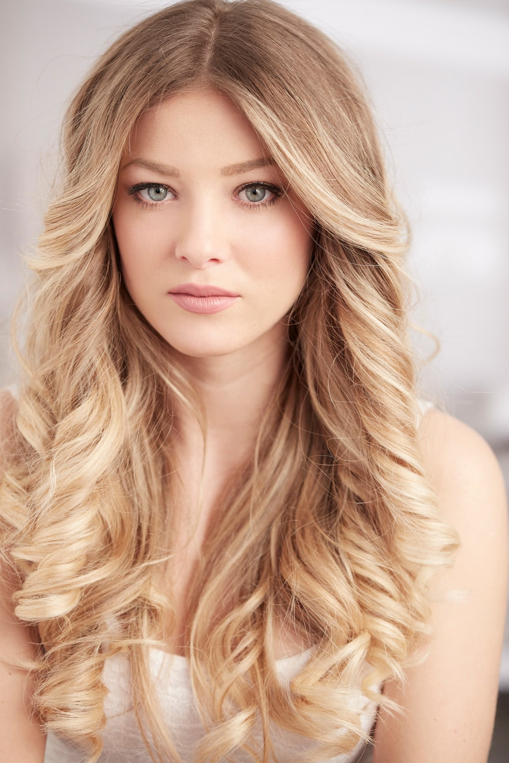 model with long dark blonde curled hair
