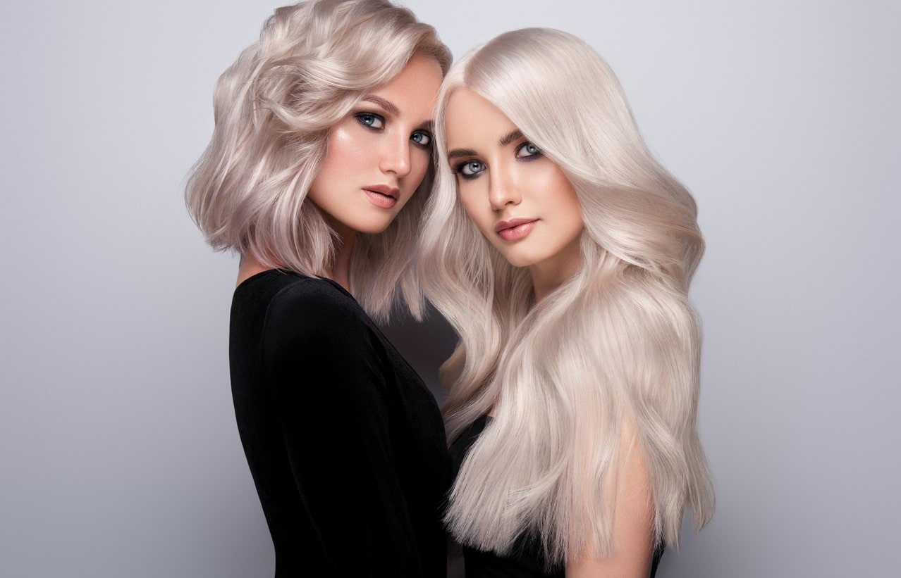 two models with light blonde hair facing each other