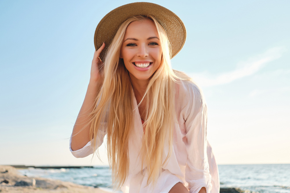 model with long blonde hair at the beach wearing a hat
