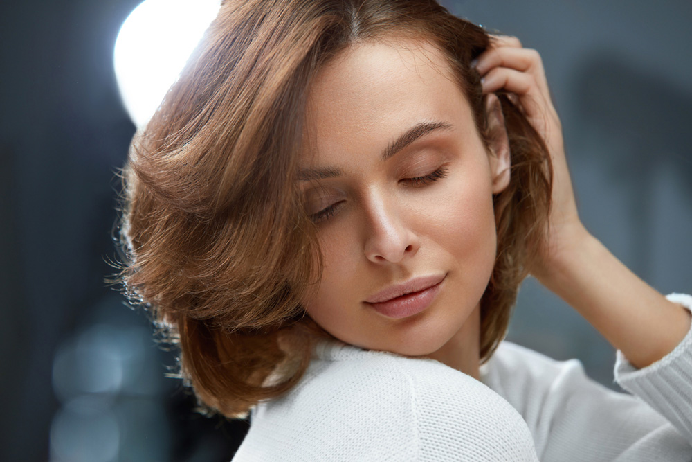 model with light brown layered hairstyle glancing downward over shoulder