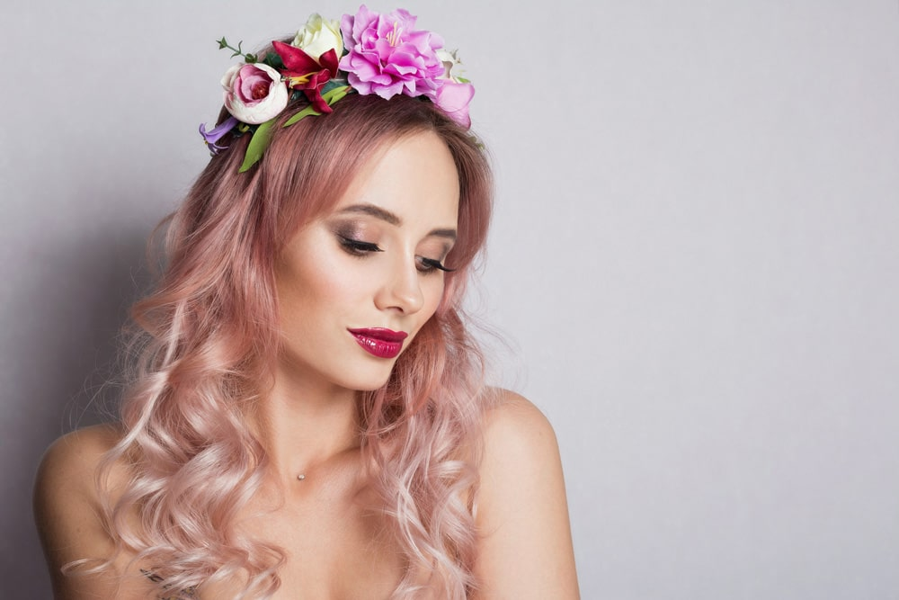 model with flowers set in long wavy light pink hair