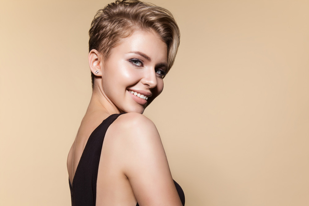 model with blonde pixie bob cut smiling over her shoulder