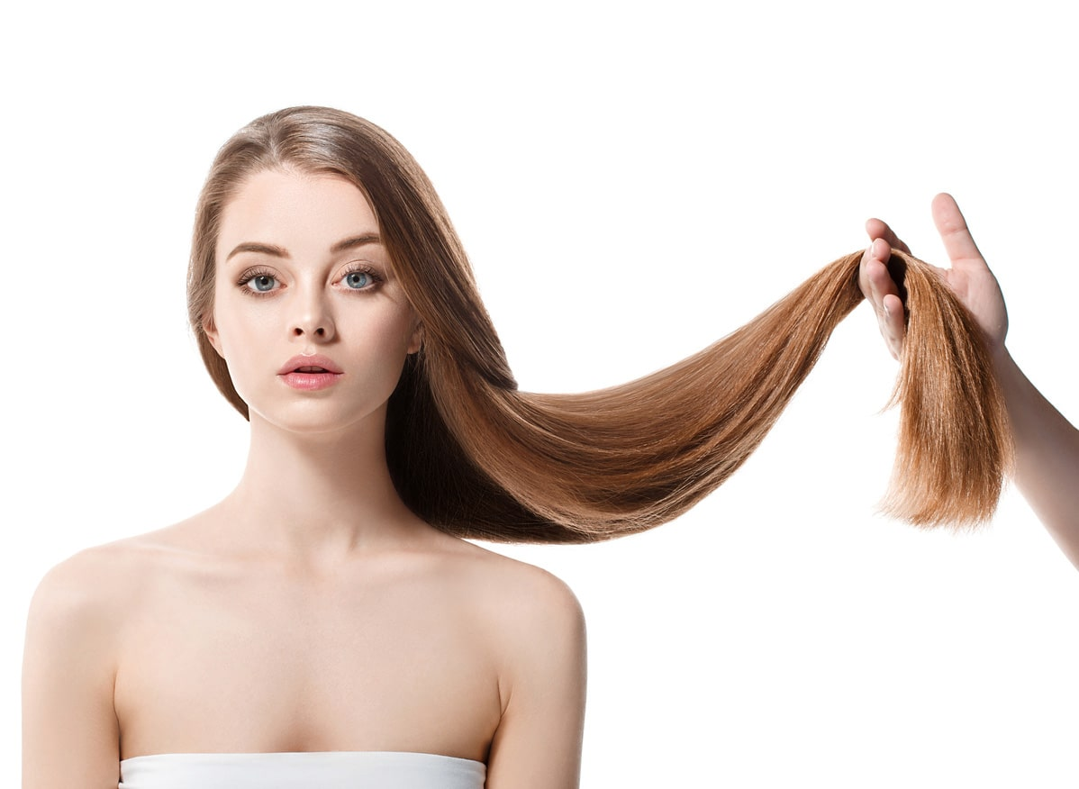 model with very long hair being held off to one side, to be trimmed at the ends