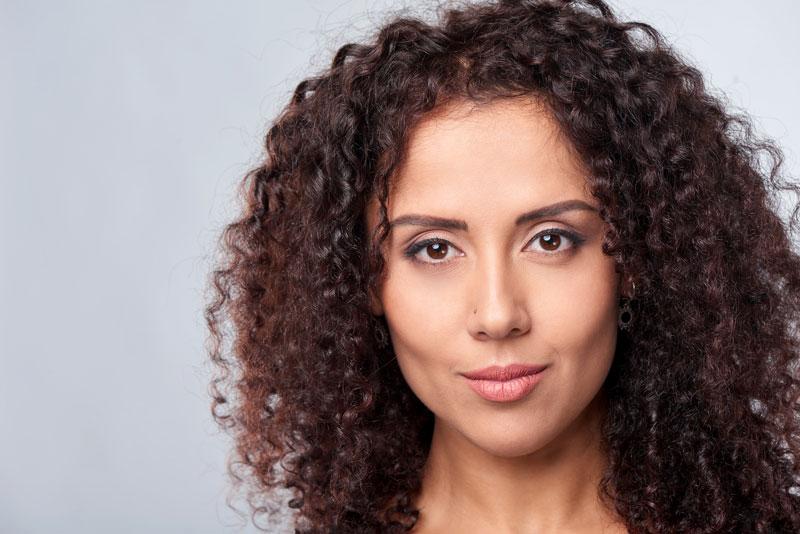 brunette model with soft curls shoulder length