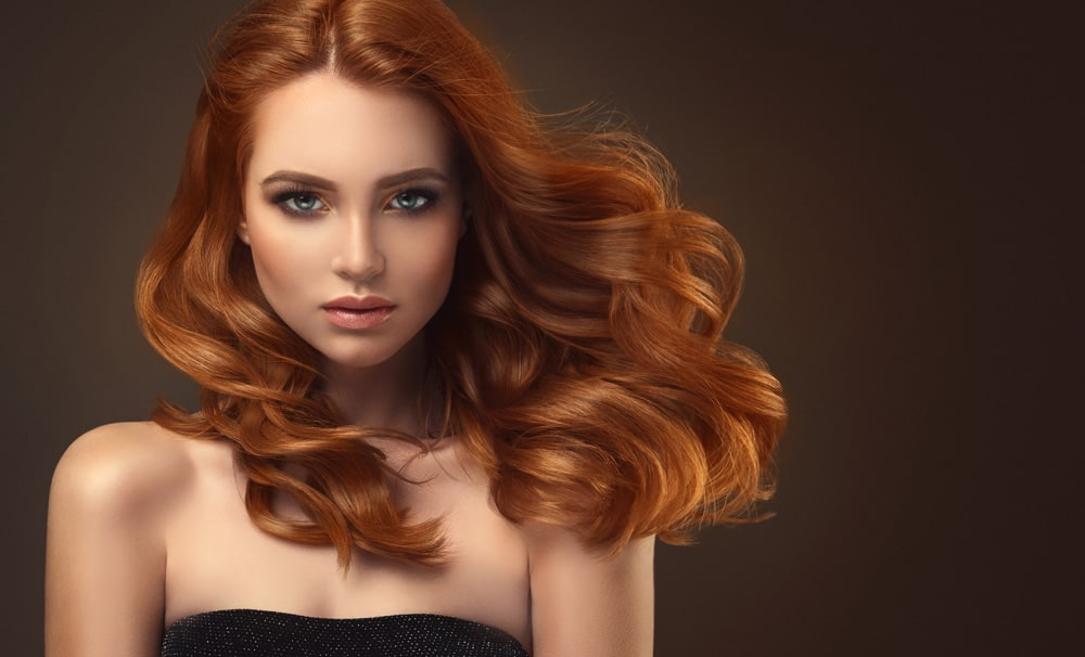model with long auburn hair blowing to the side