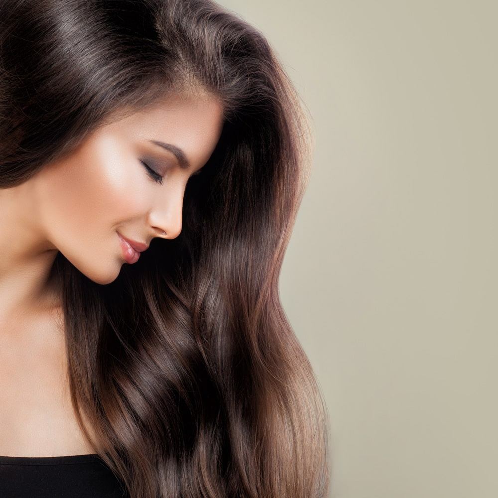 model with long brown hair laying forward over shoulder