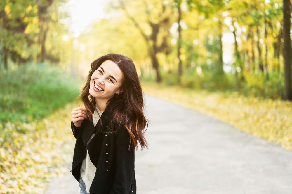 model on country road turned to camera smiling, with long brown caramel highlighted wavy hair