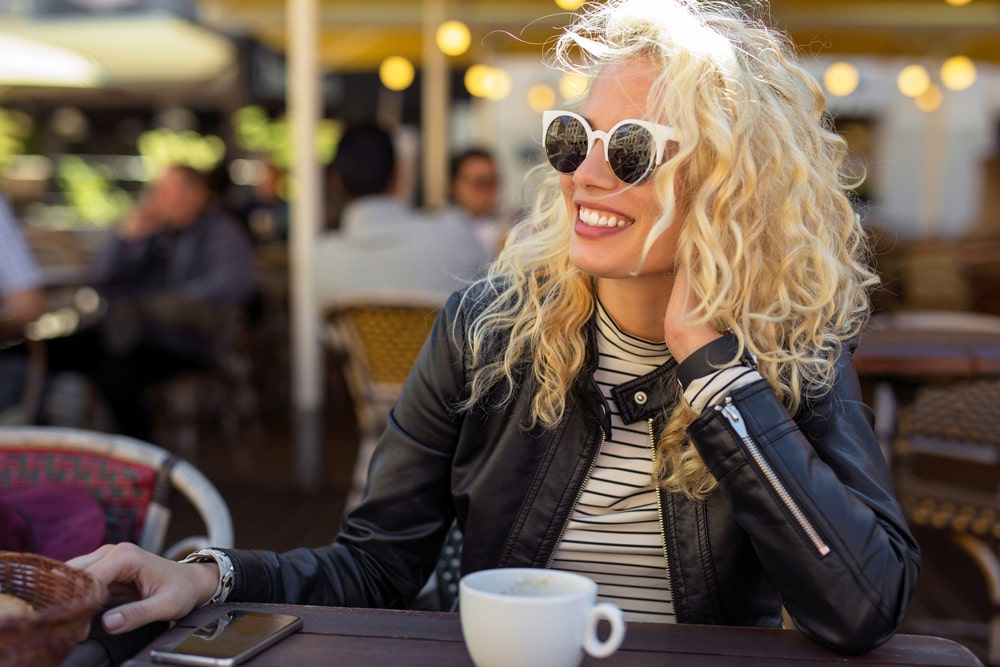 model with curly blonde hair, smiling and wearing sunglasses and leather jacket seated at outdoor dining table with cup of coffee or tea