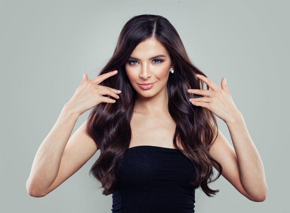 model pulling back long dark wavy hair