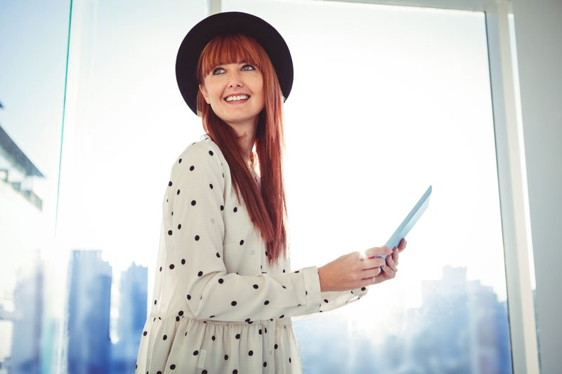 model with long straight red hair wearing brimmed hat