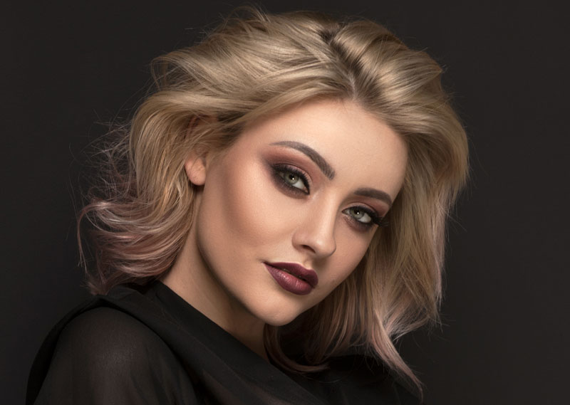 model with dark makeup and ash blonde hair in front of dark background