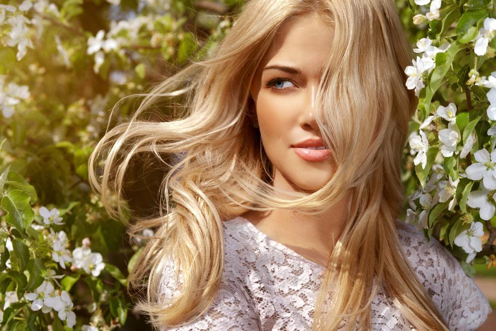 blonde model standing near flowering tree with wind blowing through hair
