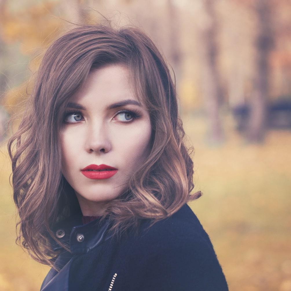model outside with shoulder length light brown hair with a lob cut