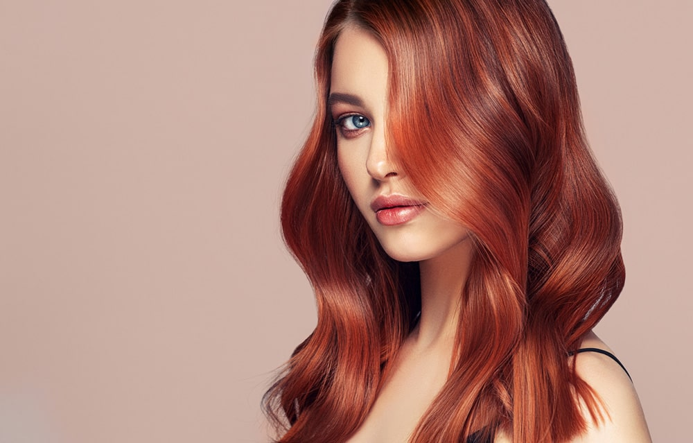 model with long red wavy hair covering left side of face