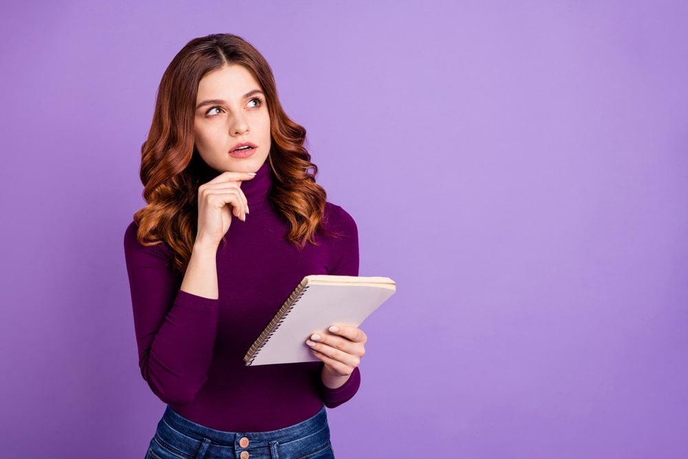 model with shoulder length red hair posing with notepad in thinking pose wearing a dark purple sweater