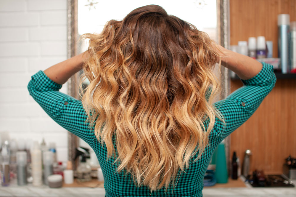 model with long wavy sandy blond hair viewed from behind with hands lifting up hair on each side